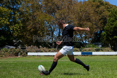 determined rugby player kicking ball on