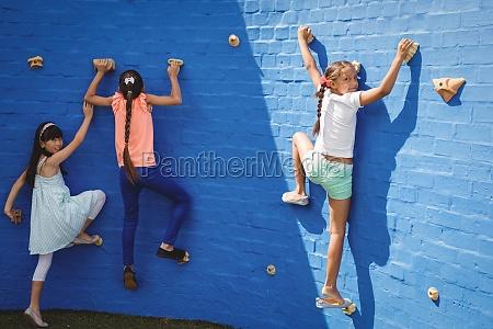 happy kids climbing wall