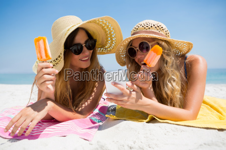 female friends using smart phone while