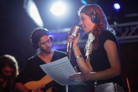 singer wearing headphones while singing at