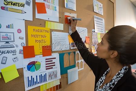 female executive writing on sticky note