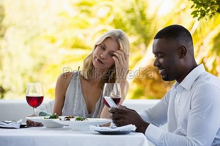 irritated woman looking at man using