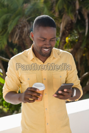 man using mobile phone while holding