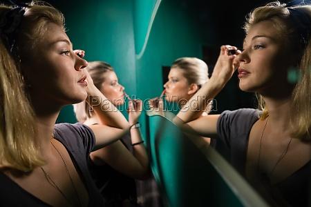 woman applying eyeliner while looking at