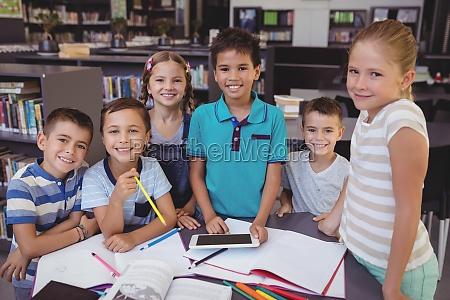 portrait of smiling schoolkid using digital