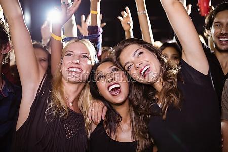 cheerful female friends enjoying at music