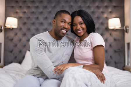 happy young couple sitting on bed