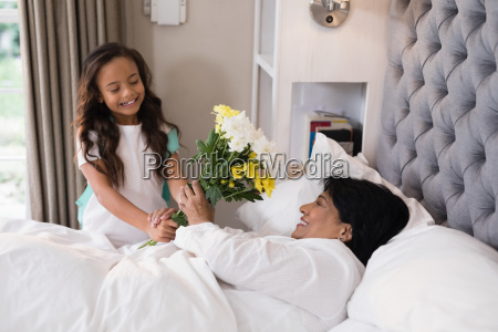 smiling girl giving bouquet to sick