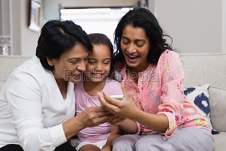 happy multi generation family using mobile