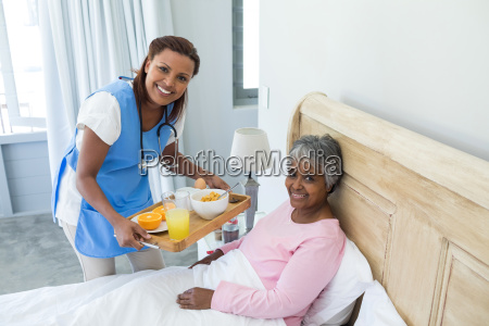 smiling female doctor serving breakfast to