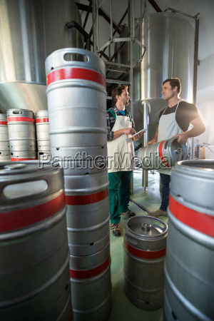 coworkers discussing while standing by vats