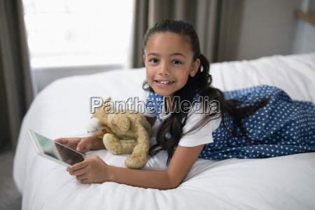 smiling girl using digital tablet while