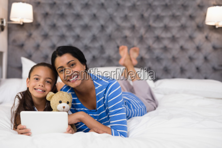 smiling mother and daughter using digital
