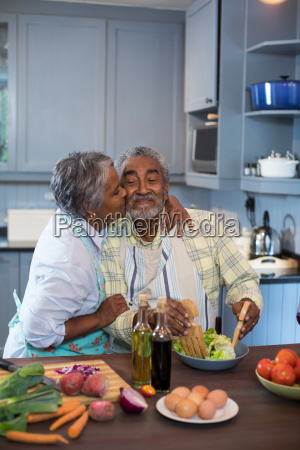 side view of woman kissing man
