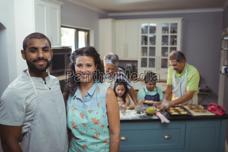 couple smiling at camera while family