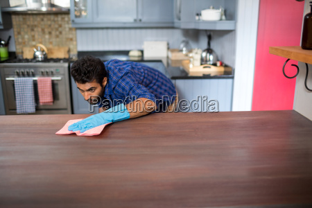 young man cleaning table with napkin