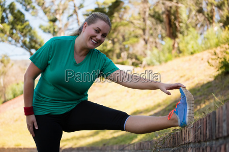 woman performing stretching exercise during obstacle