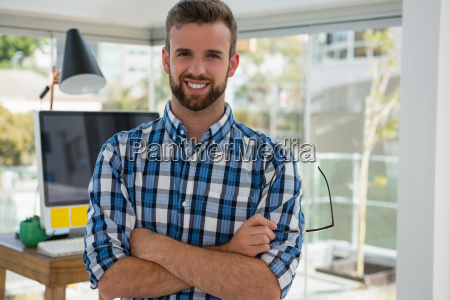 portrait of smiling businessman standing in