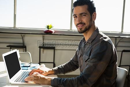 portrait of man using laptop at