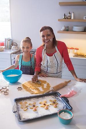 smiling mother and daughter preparing cookies