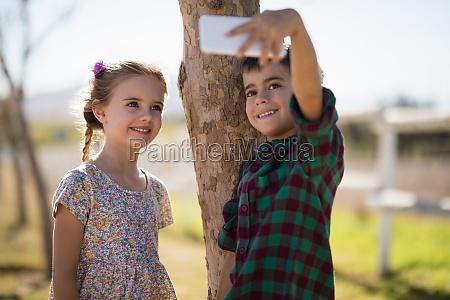 happy siblings taking selfie on mobile