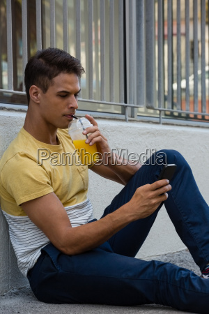 young man having drink while using