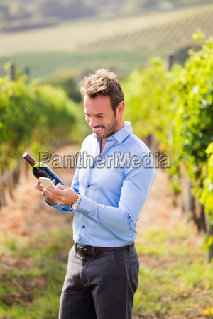 smiling man with wine bottle using