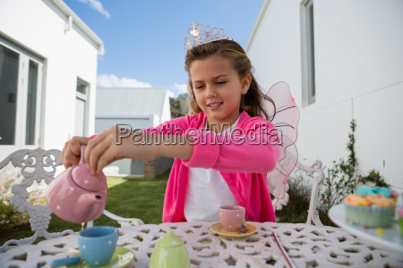 girl in fairy costume pouring coffee