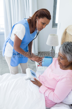 female doctor measuring blood pressure of