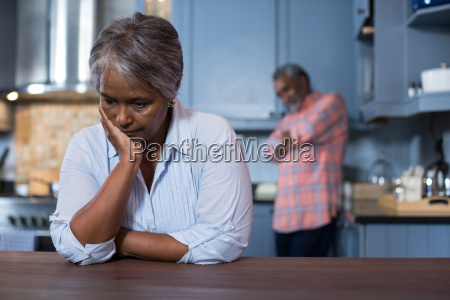 sad woman with man in background