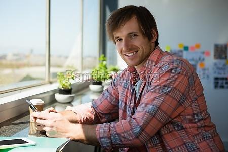 portrait of smiling man using phone