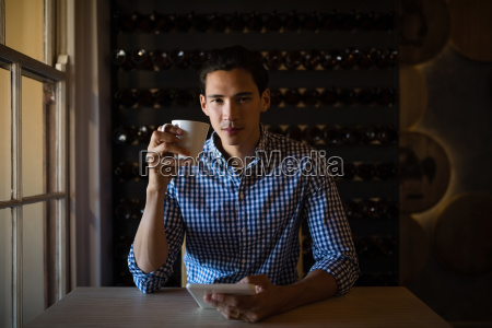 man holding digital tablet and coffee