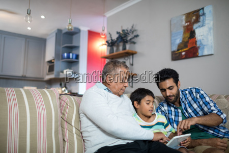father and grandfather pointing on tablet