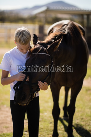 smiling girl caressing the horse in