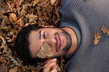 overhead of man lying on autumn