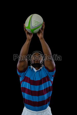 sportsman catching ball while playing rugby
