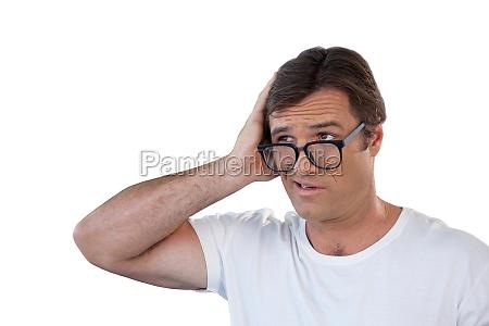 confused mature man wearing eyeglasses looking