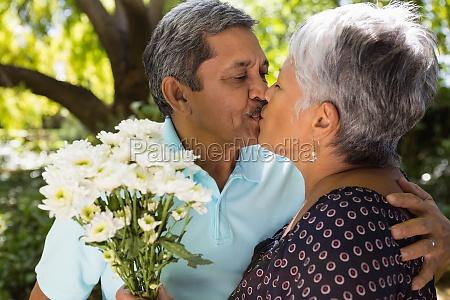 senior man kissing while giving flowers