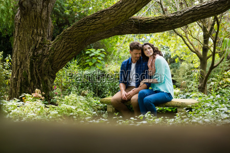 romantic couple sitting on bench in