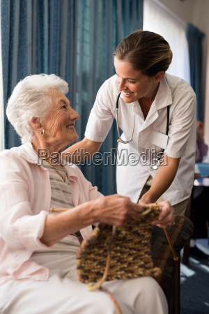 smiling senior woman knitting while looking