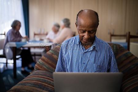 smiling senior man using laptop while