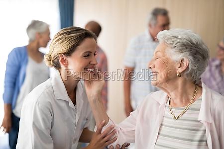senior woman touching smiling female doctor