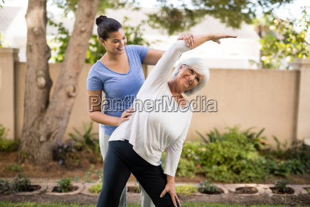 smiling trainer assisting senior woman with