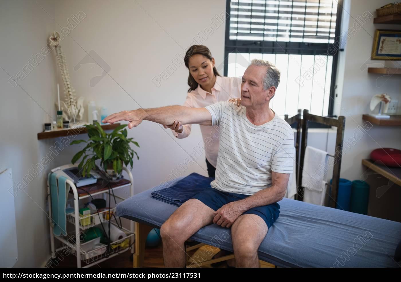 female, doctor, examining, shoulder, of, senior - 23117531