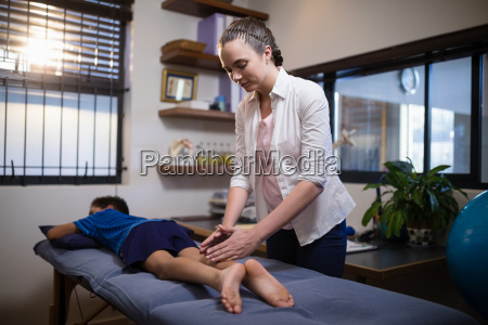 young female therapist massaging calf of