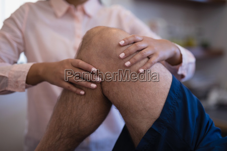 midsection of female therapist examining knee