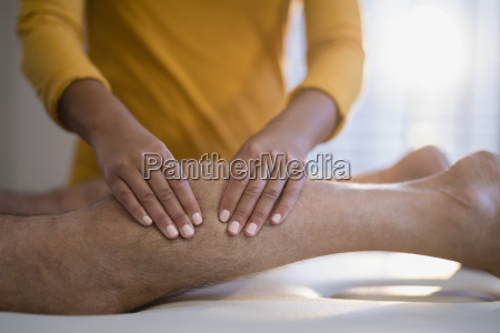 midsection of female therapist massaging calf