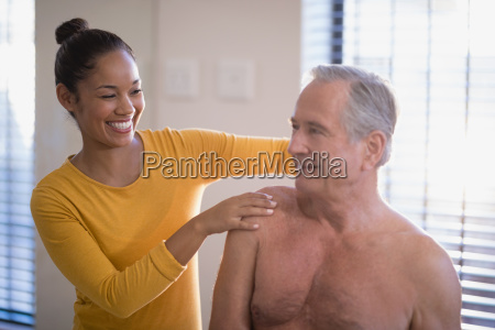 smiling female therapist giving neck massage