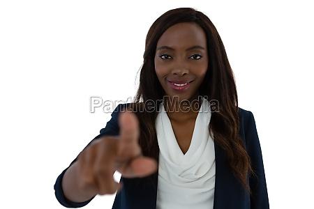 smiling young businesswoman touching imaginary screen