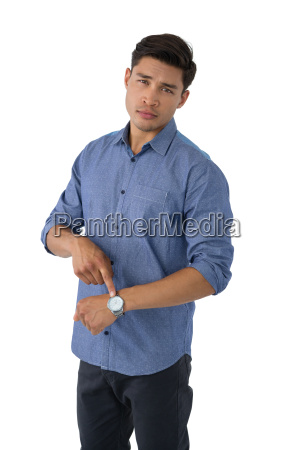 portrait of young businessman showing time